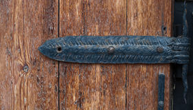 Wrought iron hinge on an old wooden door Royalty Free Stock Photo