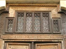 wrought-iron-ornamentation-above-carved-wooden-door Royalty Free Stock Image