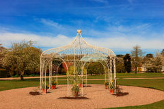 Wrought iron pergola in a park. White painted arbor in a landscaped park Royalty Free Stock Photos