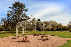 Wrought iron pergola in a park. White painted arbor in a landscaped park Royalty Free Stock Photo