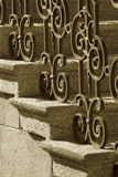 Wrought iron railing. A sepia image of wrought iron handrail and stone steps royalty free stock photos