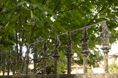 Wrought Iron Railing coated in cobwebs. Tops of wrought Iron railing coated in cobwebs and green algae under a canopy of shady trees along a walking path in Stock Photo