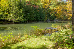 Wrought Iron Table and Chairs Near a Pond Royalty Free Stock Images