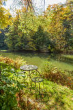 Wrought Iron Table and Chairs Beside a Small Pond Royalty Free Stock Photography