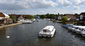 View of the river Bure at Wroxham with Broads cruise. WROXHAM, NORFOLK, ENGLAND - MAY 10, 2018: View of the river Bure at Wroxham with Broads cruise royalty free stock photography