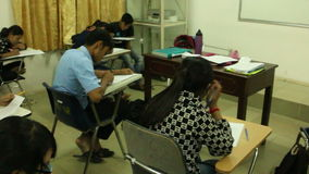 WS of Asian University students taking a midterm exam, with slow pan from hi. Wide shot of University students taking a midterm exam, with slow pan from high stock video