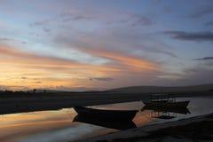Wschód słońca łodzie przy jaśnienie plażą Fotografia Royalty Free