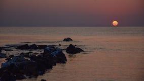Wschód słońca na brzeg morze śródziemnomorskie z pomarańczowym słońcem i kamieniami wynika morze, obrazy royalty free