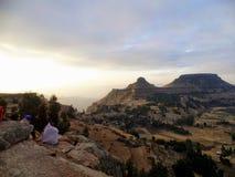 Wschód słońca na Hudad pasmie górskim na zewnątrz Lalibela Etiopia Lokalni wieśniacy biorą odpoczynek od ich wycieczkować Zdjęcia Stock