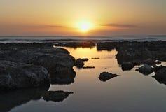Wschód słońca nad śródziemnomorskim, z dramatycznym niebem i skalistymi basenami odbija promienie w przedpolu, Cala bona, Mallorc zdjęcia stock