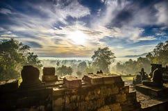Wschód słońca nad antyczną świątynią gubjącą w dżungli Borobudur obrazy royalty free