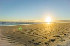 Wschód słońca nad szeroką płaską piaskowatą plażą przy Ohope Whakatane obrazy stock
