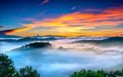 Wschód słońca nad zboczem jako słońca wydźwignięcie od horyzontu odbija lekkiego jaskrawego żółtego niebo Obraz Stock