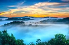 Wschód słońca nad zboczem jako słońca wydźwignięcie od horyzontu odbija lekkiego jaskrawego żółtego niebo Obrazy Royalty Free