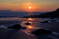 Wschód słońca odbijający w mokrym piasku i skały Słodkowodny wschód wyrzucać na brzeg Obrazy Royalty Free