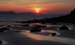Wschód słońca odbijający w mokrym piasku i skały Słodkowodny wschód wyrzucać na brzeg Obrazy Stock