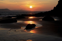 Wschód słońca odbijający w mokrym piasku i skały Słodkowodny wschód wyrzucać na brzeg Obraz Royalty Free