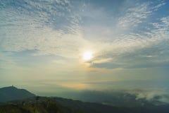 Wschód słońca przy górą z mgłą i chmurami w niebieskim niebie Zdjęcia Royalty Free