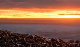 Wschód słońca przy otoczak plażą obrazy stock