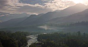 Wschód słońca wśród rzeki i gór Obrazy Stock