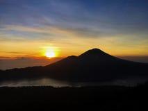 Wschód słońca w górach Powstający słońce w niebie, puszystych chmurach, odległych górach i powulkanicznym jeziorze pomarańcze i s Obrazy Royalty Free
