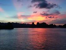 Wschód słońca w Halong zatoce Z pomarańczowych i błękita brzmieniami Z niektóre statkami przy tłem obrazy royalty free