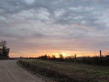 Wschód słońca wzdłuż wiejskiej drogi z Poruszonymi Falowymi chmurami Fotografia Royalty Free