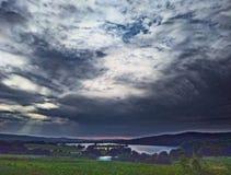 Wschód słońca z burz chmurami nad iskrzastym jeziorem fotografia royalty free