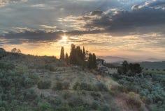 Wschód słońca z chmurami na dom na wsi Tuscany Obraz Stock