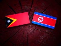 Wschodnia Timorese flaga z koreańczyk z korei północnej flaga na drzewnym fiszorku Obrazy Stock
