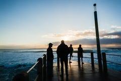 Wschodu słońca oceanu fala mola ludzie Obrazy Royalty Free