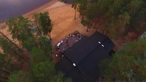 Wsi chałupa na plażowym pobliskim jeziorze przy wieczór świętowaniem outdoors Ludzie zabawę i tana na pokładzie z zbiory wideo