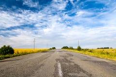 Wsi droga wśród poly piękny zachmurzone niebo Obraz Stock