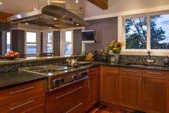 Współczesny ekskluzywny domowy kuchenny wnętrze z drewnianymi gabinetami, benzynową kuchenką, wentylacja kapiszonem i widoków okn obraz stock