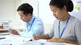 Współpracownicy etniczni zajmujący się badaniami naukowymi siedząc i pisząc przy stole biurowym zdjęcie wideo