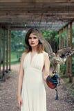 Wspaniała młodej kobiety brunetka z koczka ostrzyżenia mienia jastrzębia ptaka outdoors portretem fotografia royalty free