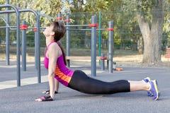 Wspaniała szczupła młoda kobieta ćwiczy joga przy plenerowym sportsground Kobry asana Calmness i relaksuje, rozciągający Prawdziw fotografia stock