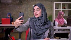 Wspaniała arabska kobieta jest szarymi hijam wp8lywy selfies na jej smartphone podczas gdy siedzący przy miejsce pracy, kolega dz