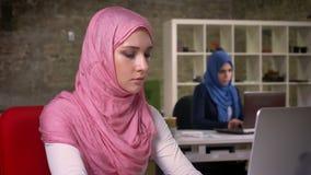 Wspaniała arabska kobieta w różowym hijab siedzi w cegły światła biurze i używa jej pracującego komputer, koledzy w hijabs