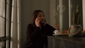 Wspaniała azjatykcia dziewczyna opowiada na mądrze telefonie w domu zdjęcie wideo