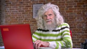 Wspaniała babcia z biel długą brodą włosy i pisać na maszynie na czerwonym komputerze podczas gdy siedzieć w ceglanym studiu skup