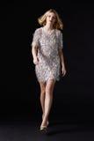 Wspaniała blondynki kobieta chodzi w kierunku kamery, czarny tło fotografia royalty free