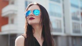 Wspaniała brunetki kobieta z namiętnymi czerwonymi wargami i nosa przebijania spojrzeniami kamera, i stawia dalej okulary przeciw zdjęcie wideo