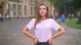 Wspaniała caucasian kobieta stoi z jej rękami na biodrach i gwarantującym spojrzeniem przy kamerą, miasta tło, dzień