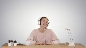 Wspaniała dama w różowego puloweru słuchającej muzyce w hełmofonach i ono uśmiecha się kamera na gradientowym tle zdjęcie wideo