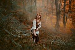 Wspaniała dama z długim czerwonym włosy w skór ubraniach podąża dzikiego zwierzęcia, tropi puszka zdobycza w tropikalnym lesie de obrazy stock