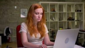 Wspaniała dosyć miedzianowłosa caucasian kobieta tanczy podczas gdy siedzący przy desktop i pisać na maszynie w jej laprop, skupi
