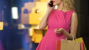 Wspaniała dziewczyna cieszy się drogiego zakupy, opowiada nad telefonem, moda butik zbiory wideo