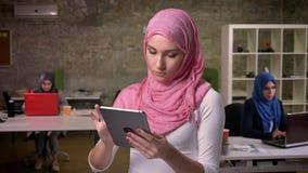 Wspaniała jest ubranym różowego hijab środkowa wschodnia kobieta swiping jej pastylkę podczas gdy stojący wśród jej kolegów na tl