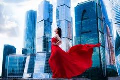 Wspaniała kobieta w czerwień trzepoczącej sukni odizolowywaj?ca poj?cie czarny wolno?? Moda obrazy royalty free